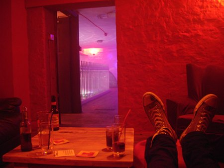 Stevie C with his converse feet up on table like in Rab C Nesbitt in the Balcony Bar chill room.